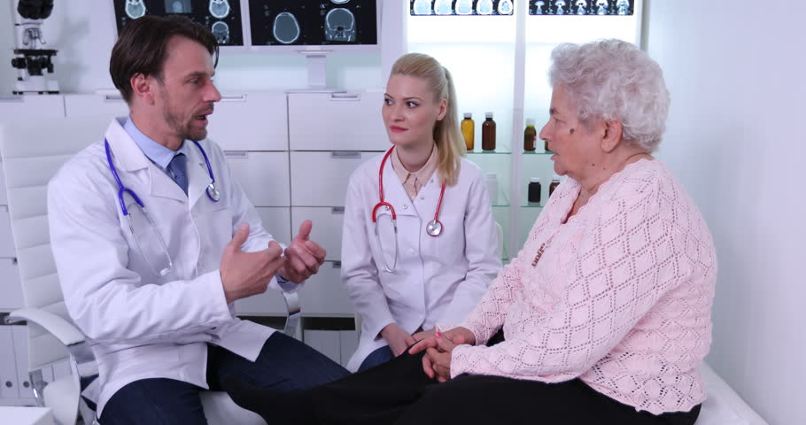 Doctor Man and Woman Talking About Therapy Procedure in Cabinet with Old Patient   Shutterstock HD Video #32903944