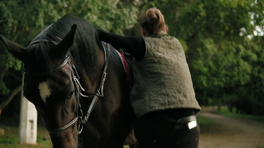 Female equestrian climbs on horseback with help of stirrup and strokes a beautiful brown horse | Shutterstock HD Video #32909869