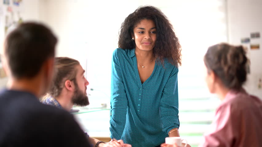 Meeting at the office of a modern, multi-ethnic company. a beautiful young black woman talking to her colleagues sitting around the table. | Shutterstock HD Video #32919805
