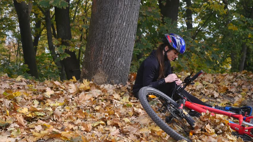A young woman sits in a park after falling from a bike, calms the pain in her knee, is a dangerous bike ride in the park on an autumn day | Shutterstock HD Video #32921677