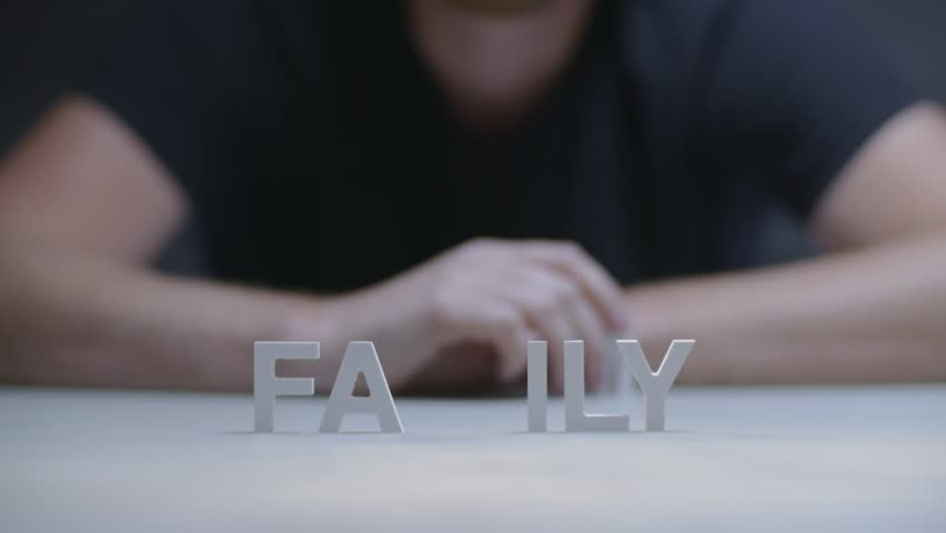 Man hands making composition word family from white letters on gray background