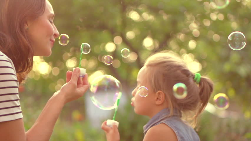 Happy Mother and her little Daughter playing together, blowing and catching soap bubbles.Beauty Mum and her Child in Park together. Family, Mother's Day Joy. Mom and Baby. Mother's Day celebrating. 4K
