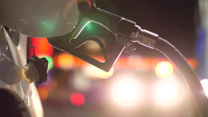 Fuel nozzle inserted in car's gas tank as it's being refueled at gas station pump at night. Closeup, shallow DOF. 4K UHD.
