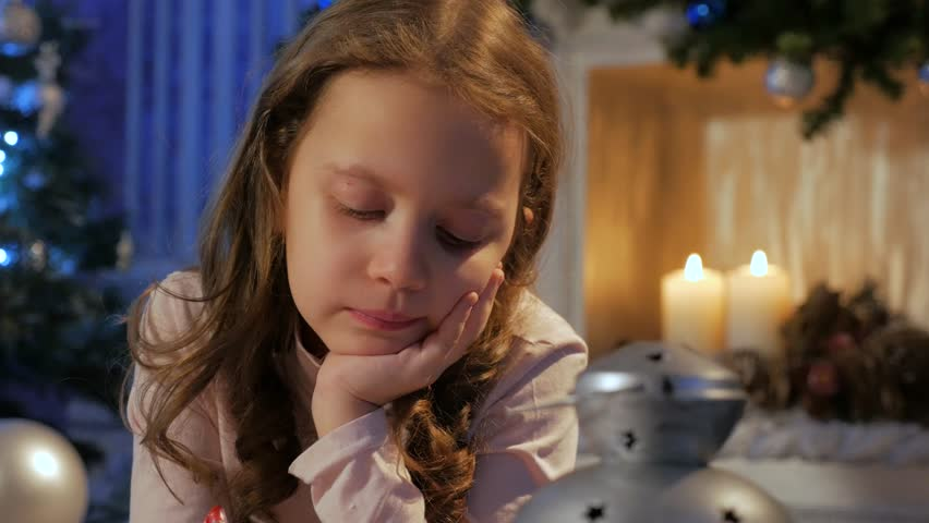 Dolly shot of cute girl writing letter to santa at living room with fireplace | Shutterstock HD Video #32936533