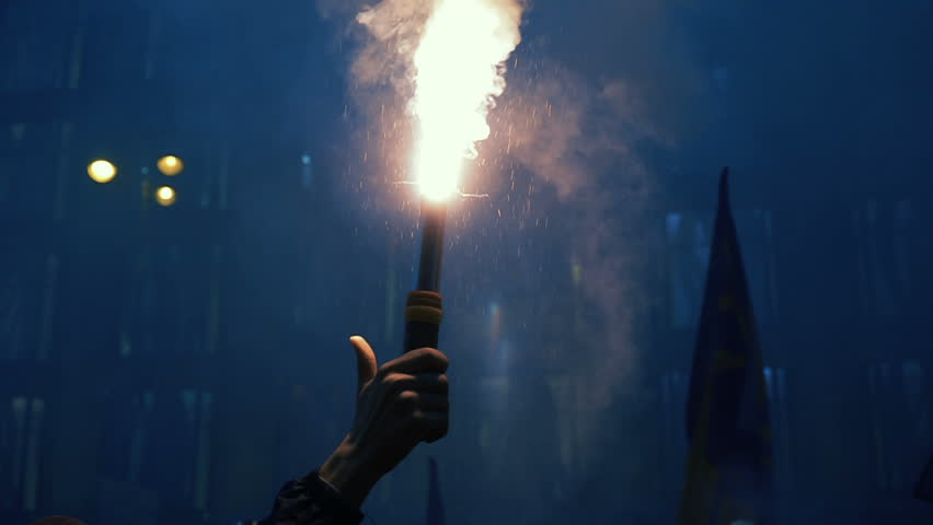 Protester holding burning flare. Night street in smoke. Hand close-up