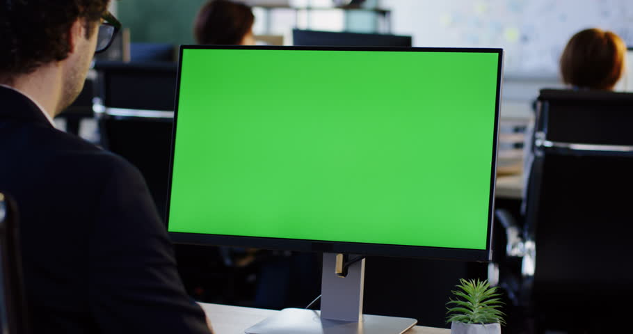 Male office employee working on the PC computer with green screen display monitor in the office room. View from behind. Chroma key. Indoors Man Work, template,Technology, Idea ,Studio ,Workplace, Job  Royalty-Free Stock Footage #32941558