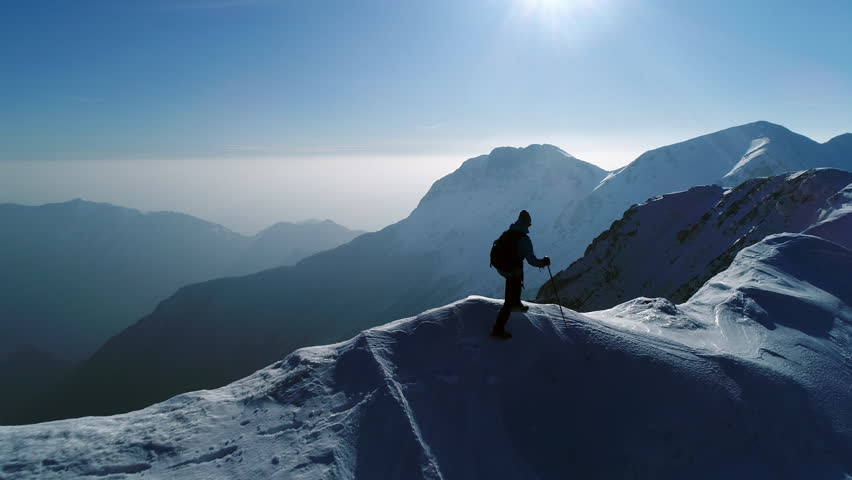 Aerial - Young man hiking on top of snowy mountain at beautiful winter sunset. Male mountaineer with trekking poles and a backpack walking on mountain ridge in Julian Alps | Shutterstock HD Video #32970271