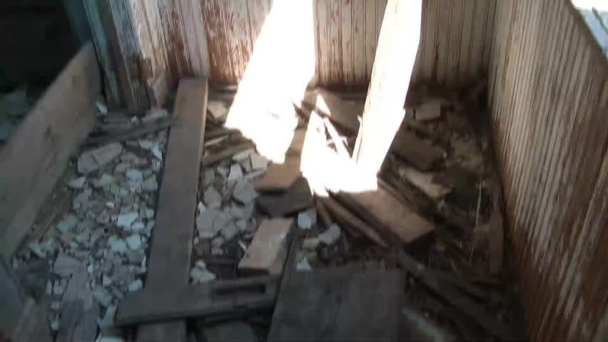 Panning of run down interior of abandoned farm home from entrance to one and only room inside structure. #3297206