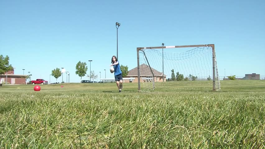 Girl stands inside goal in sunlight while foot kicks soccer ball towards her, saving one, the other bouncing off cross bar.