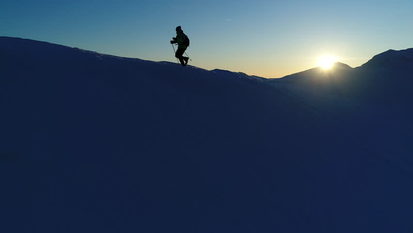 Aerial, slow motion - Extreme recreational pursuit of adult male in winter clothing running on snowy mountain top with trekking poles and a backpack at sunset. Silhouette of a man running on mountain | Shutterstock HD Video #32993587