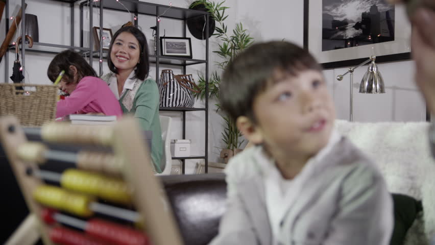 Happy family spending time together at home. Mother and father are helping their children to learn. In slow motion