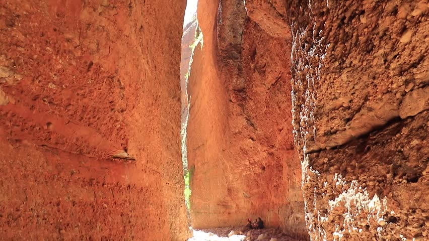 Vertical pan looking outwards towards the entrance of Echidna Chasm at midday capturing the brief moments when sunlight penetrates the chasm, Bungle Bungles, Purnululu World Heritage Listed Park. | Shutterstock HD Video #32998807