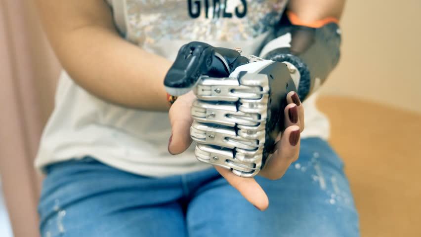 Female using futuristic robotic cyborg arm. Real modern medical robotic prosthesis.