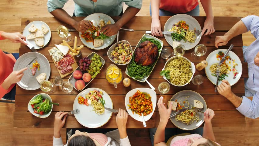 Eating and leisure concept - group of people having dinner at table with food | Shutterstock HD Video #33010741