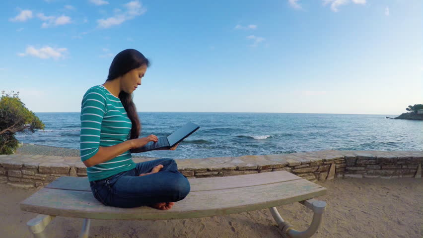 An Asian woman is chating with mobile telephone on a beach | Shutterstock HD Video #33018589