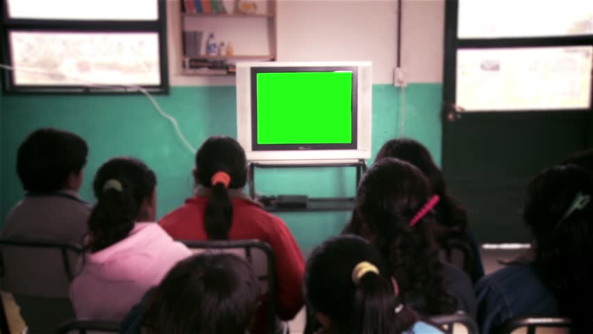 "Students in Classroom Watching Old TV with Green Screen.  You Can Replace Green Screen with the Footage or Picture you Want with ""Keying"" effect in After Effects  (check out tutorials on YouTube). 
