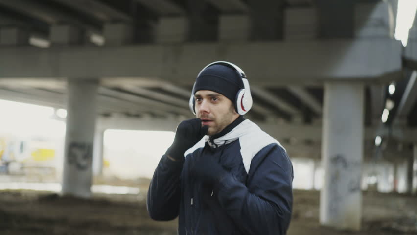 Dolly shot of sportive man boxer in headphones training punches in urban location outdoors in winter | Shutterstock HD Video #33024940