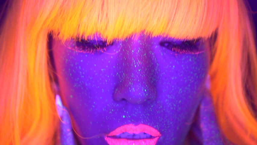 Closeup woman face and torso with fluorescent make up in orange wig, creative makeup look great for nightclubs. Halloween party, shows and music concept - slow motion video | Shutterstock HD Video #33026080