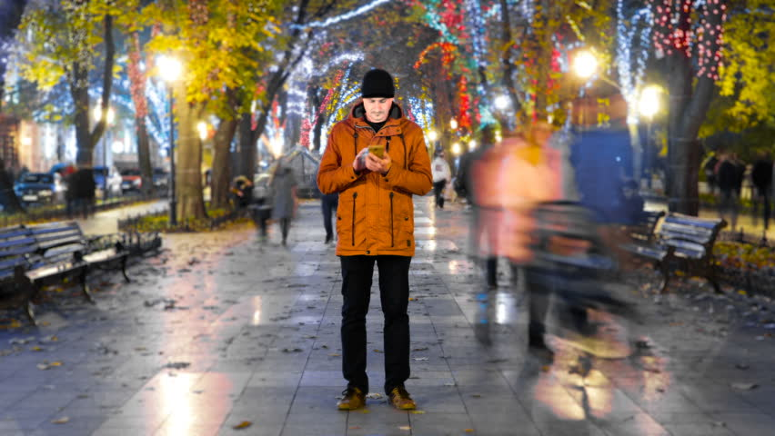 Timelapse of man standing still with smartphone on crowded walkway park boulevard with christmas garlands at night. People moving fast. Concept of flowing time and technologies Royalty-Free Stock Footage #33030538