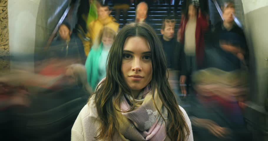 Beautiful young woman looking at camera, closeup. Moving crowd of people blurred in motion in background. 4K UHD timelapse. Royalty-Free Stock Footage #33032461