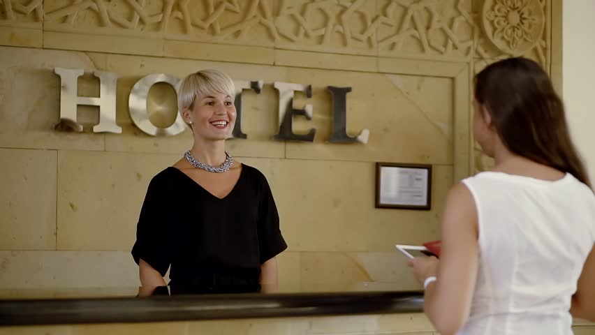 Tourist comes to the reception in the hotel and gives her passport. Receptionist politely checks her passport and gives her the form to fill.