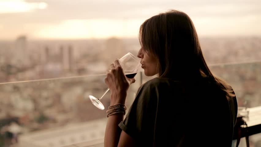 Happy woman drinking red wine while sitting in rooft bar in the city, 4K