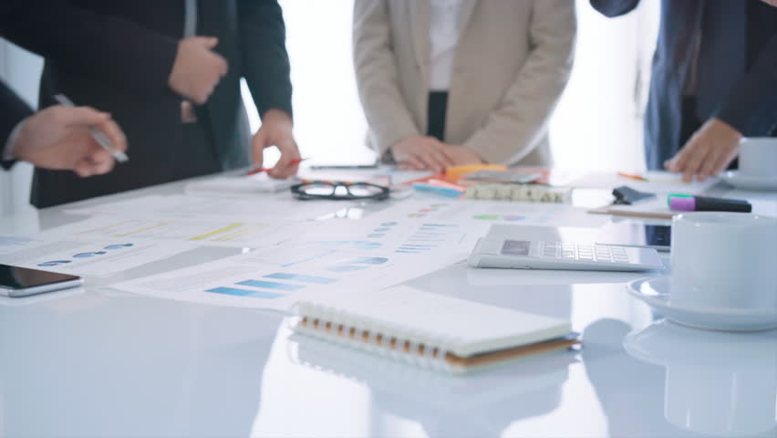 Diverse group of executives having a business meeting. They are discussing over financial data and graphs, showing the development of their company. | Shutterstock HD Video #33072127
