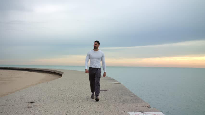 Male runner is walking along beautiful seashore while listening to the music with headphones. Ready to workout.