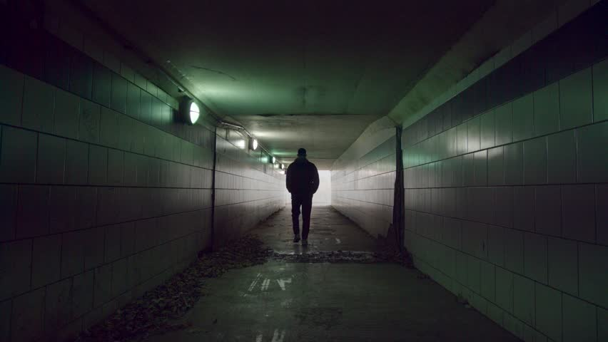 Man is walking to the end of the tunnel. Light at the end of the tunnel. | Shutterstock HD Video #33075337