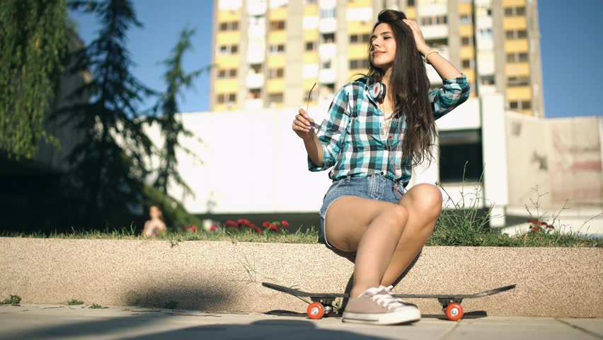 Pretty girl in checkered shirt putting on her sunglasses | Shutterstock HD Video #33079618
