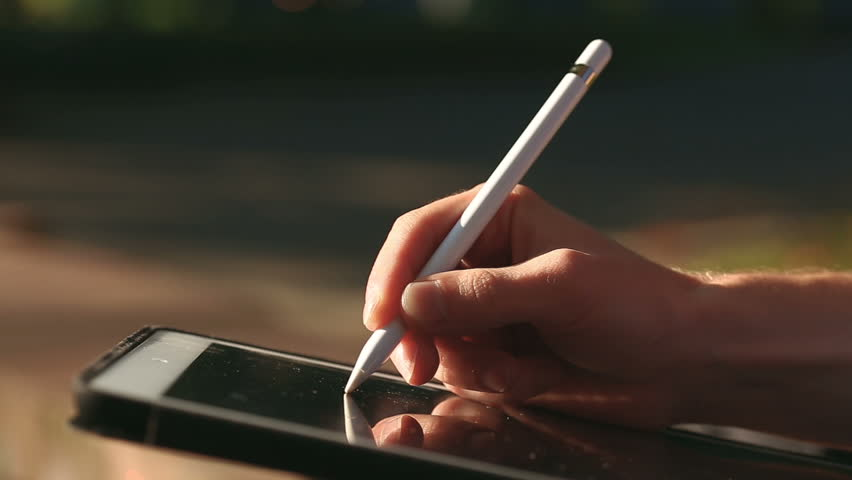 Closeup shot of painter's hand drawing a sketch on tablet using stylus at park.  | Shutterstock HD Video #33082753