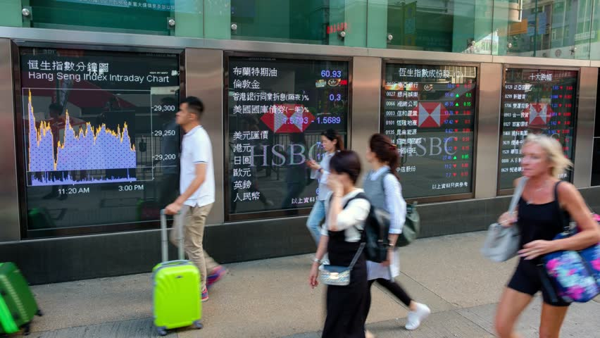 Hong Kong - November 17, 2017: Pedestrians walk past a financial display board in Mong Kok, Hong Kong, China.- time lapse