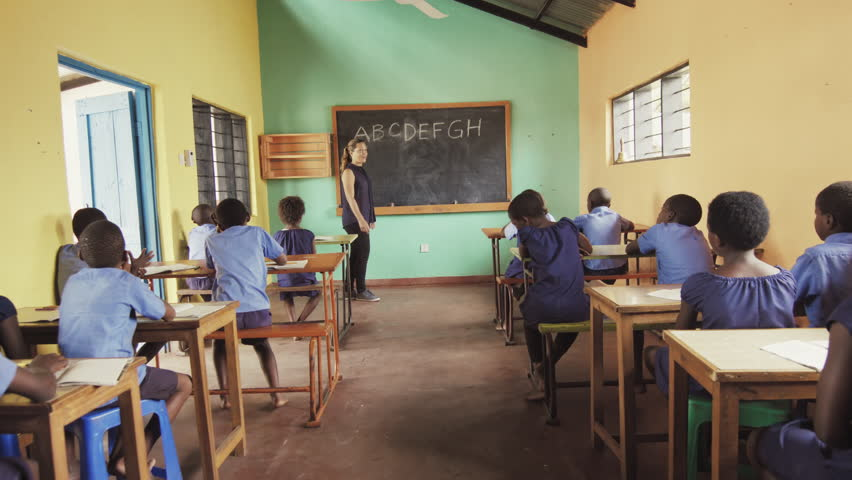 4k back view of school classroom of African students / pupils raising hands to answer teachers question, learning english language alphabet off chalkboard.