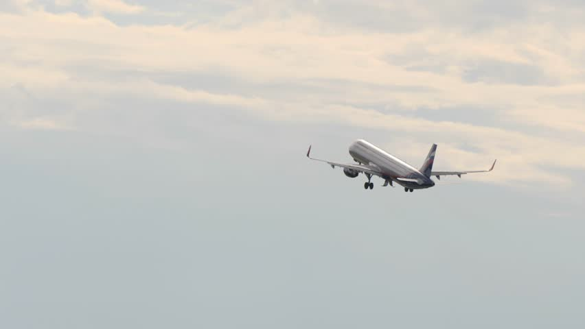 Passanger airplane retracts landing gear after take off and flies away in overcasted sky