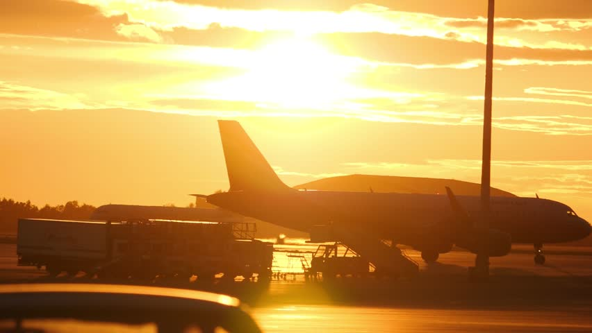Airplain taxiing at airport ramp and ground support equipment against sunset sky