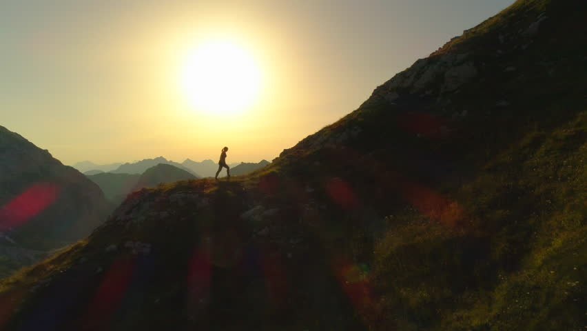 AERIAL SILHOUETTE COPY SPACE Flying along unknown female hiker walking uphill in dusky mountain range. Young woman trekking up steep hillside in beautiful amber nightfall. Picturesque mountain ascent | Shutterstock HD Video #33099910