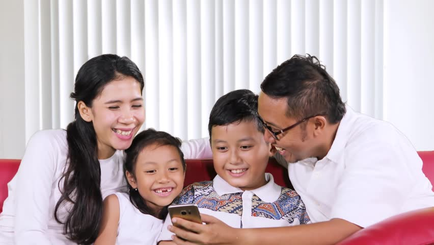 Happy family using a smartphone together while chatting and sitting on the sofa in the living room at home #33101380