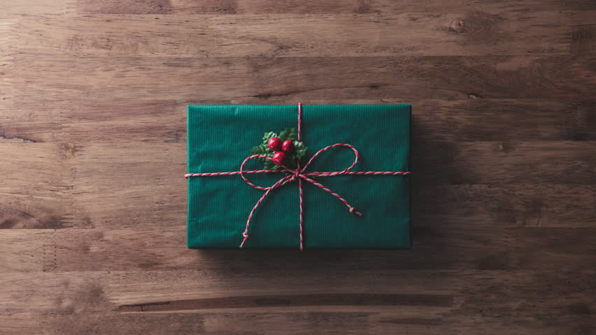 Colorful alternate Christmas and New Year holidays gift boxes on wood table with blank space at the end - top view, stop motion