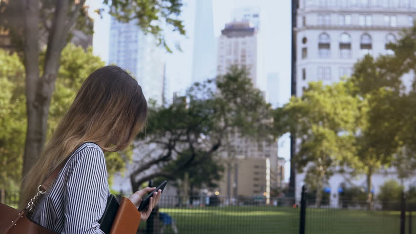 Young busy businesswoman walking to the work, holding the documents and using smartphone in New York, America. | Shutterstock HD Video #33104995
