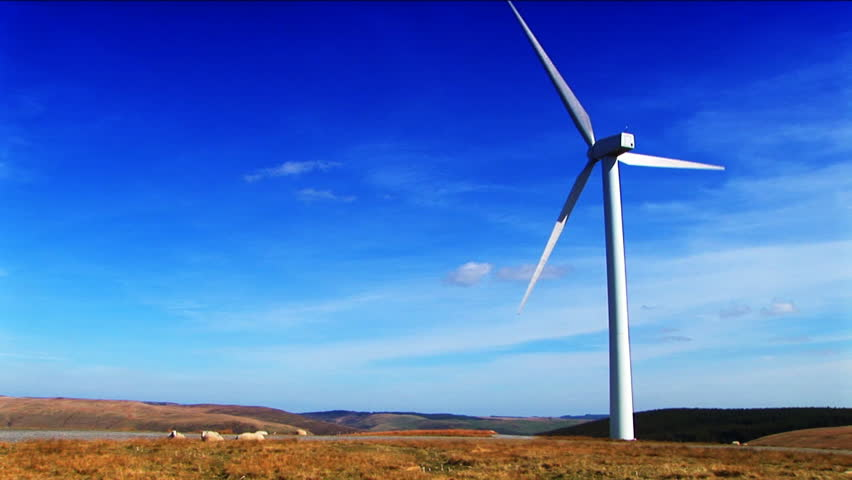 single wind turbine on hill blue sky
