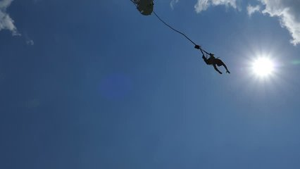 Man is jumping from the top of a Bungee Jumping - Slow Motion; Exhilarating bungee jump from the high platform above sea level, slow motion video clip.