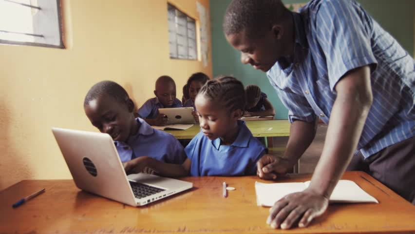 4k of teacher instructing African school students / pupils to use laptop computer in classroom. #33160741