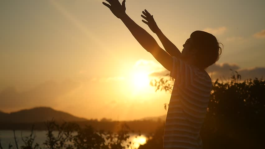 Young man wearing sunglasses raising arms to the rising sun at beautiful sunset on top of the mountain in Slow Motion. 1920x1080 #33165583