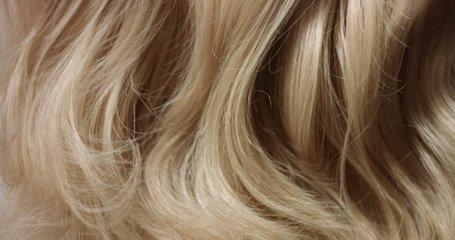 Tilt video of woman's long wavy blond hair on white background