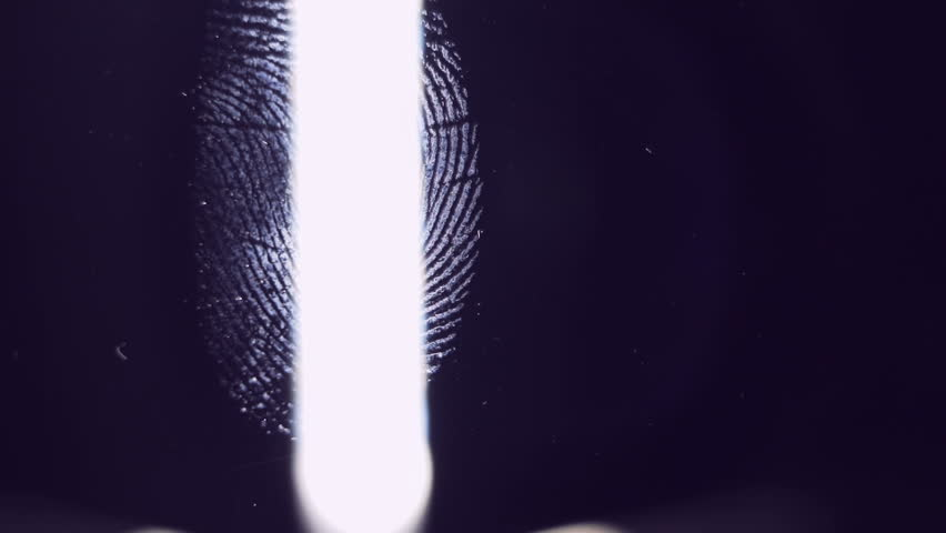 The forensic scientist examines the evidence. Fingerprints close-up. The detective uses a bright light source.
