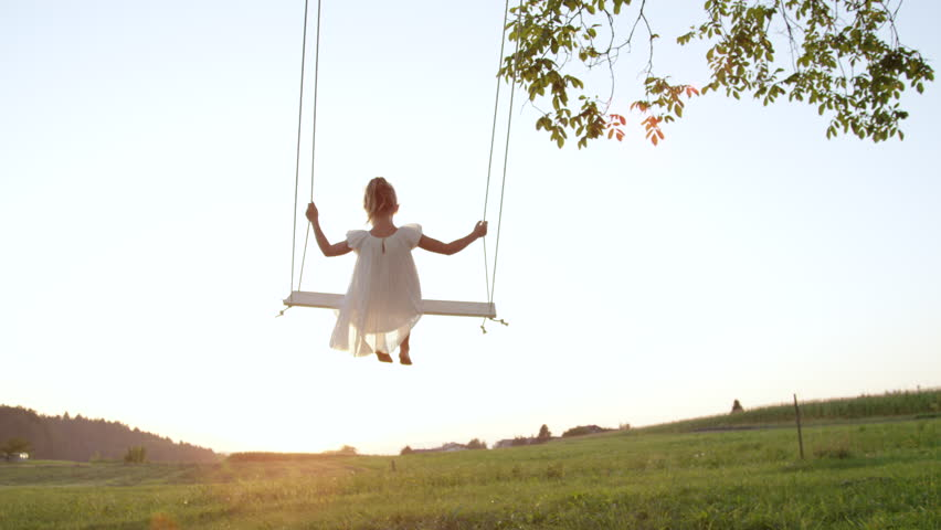 SLOW MOTION CLOSE UP Unrecognizable little girl swaying on a wooden swing on a warm summer evening. Girl in a flowing white dress enjoying sunset. Barefoot child on a swing looking at the setting sun. Royalty-Free Stock Footage #33179689