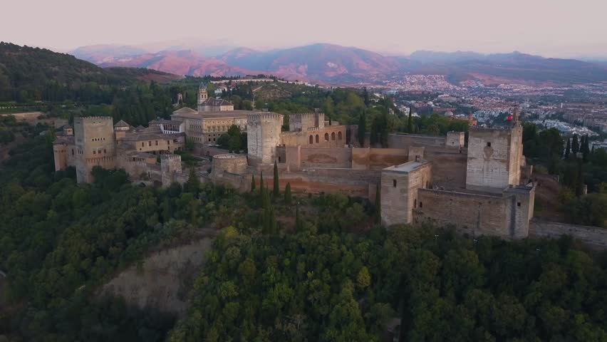 4k aerial drone footage - Ancient medieval castle, The Alhambra, of Granada Spain at sunset.  This mighty fortress was built by the Moorish Caliphate when they controlled much of Spain.