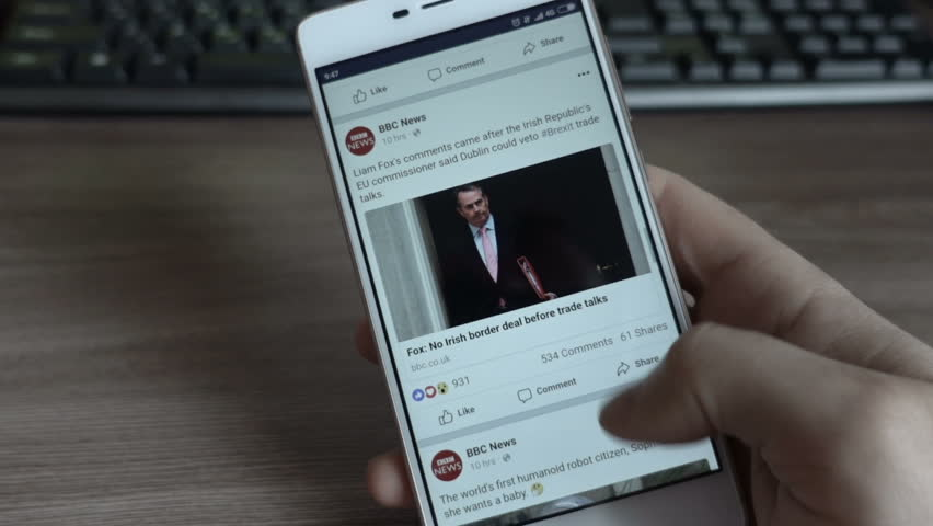 Man using his smartphone with to scroll a Facebook account feed, scrolling news BBC, tapping on screen.
