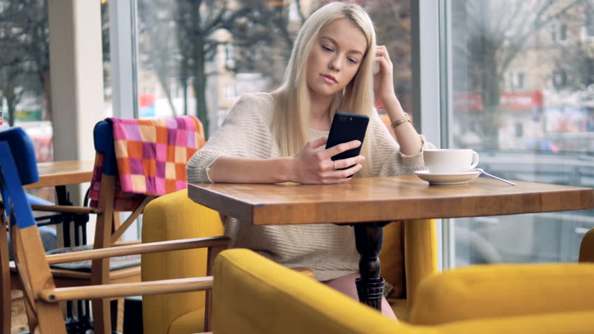 A woman uses a smartphone in a coffee shop and thinks.