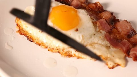 Serving fried egg with bacon on plate